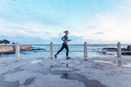 Woman athlete running outdoors along the sea