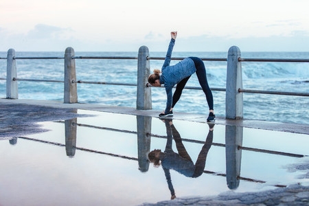 Woman doing stretching workout on wet road