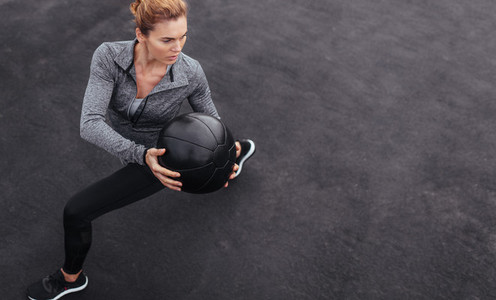 Sportswoman stretching outdoors with medicine ball
