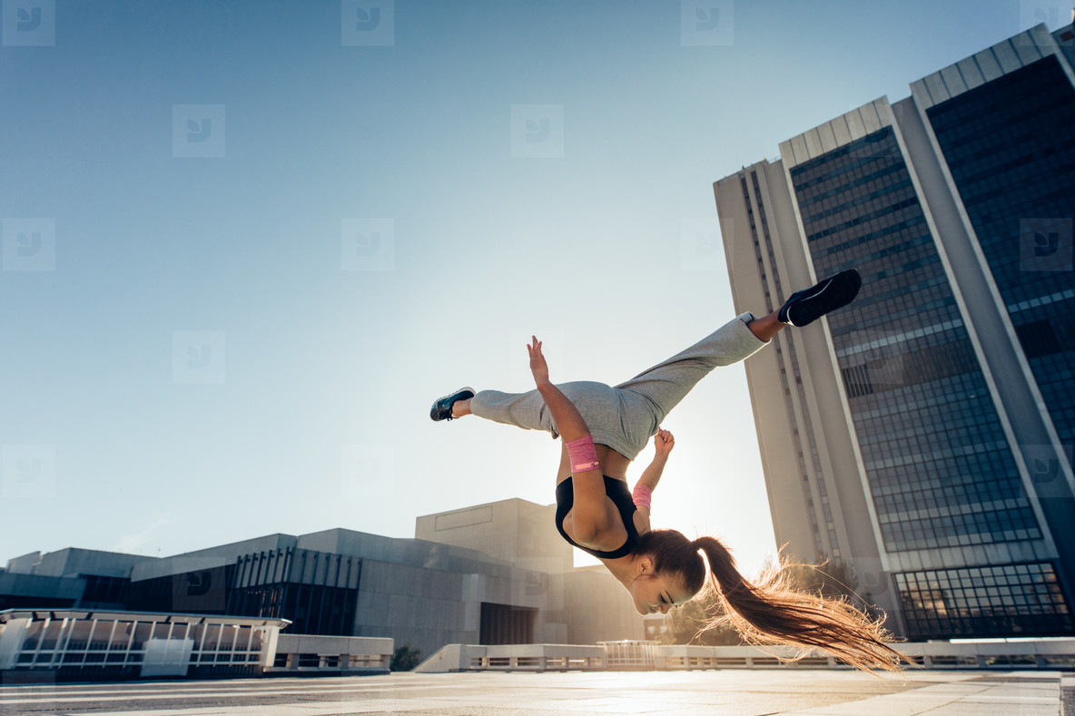 Woman doing frontflip outdoors in city