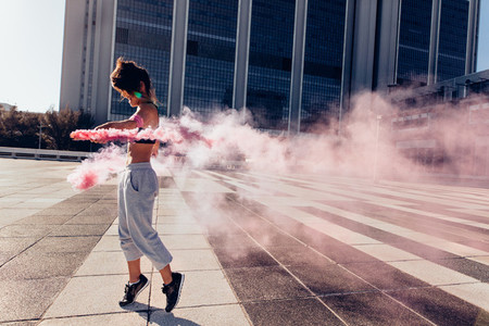 Woman with smoke grenade outdoors in city
