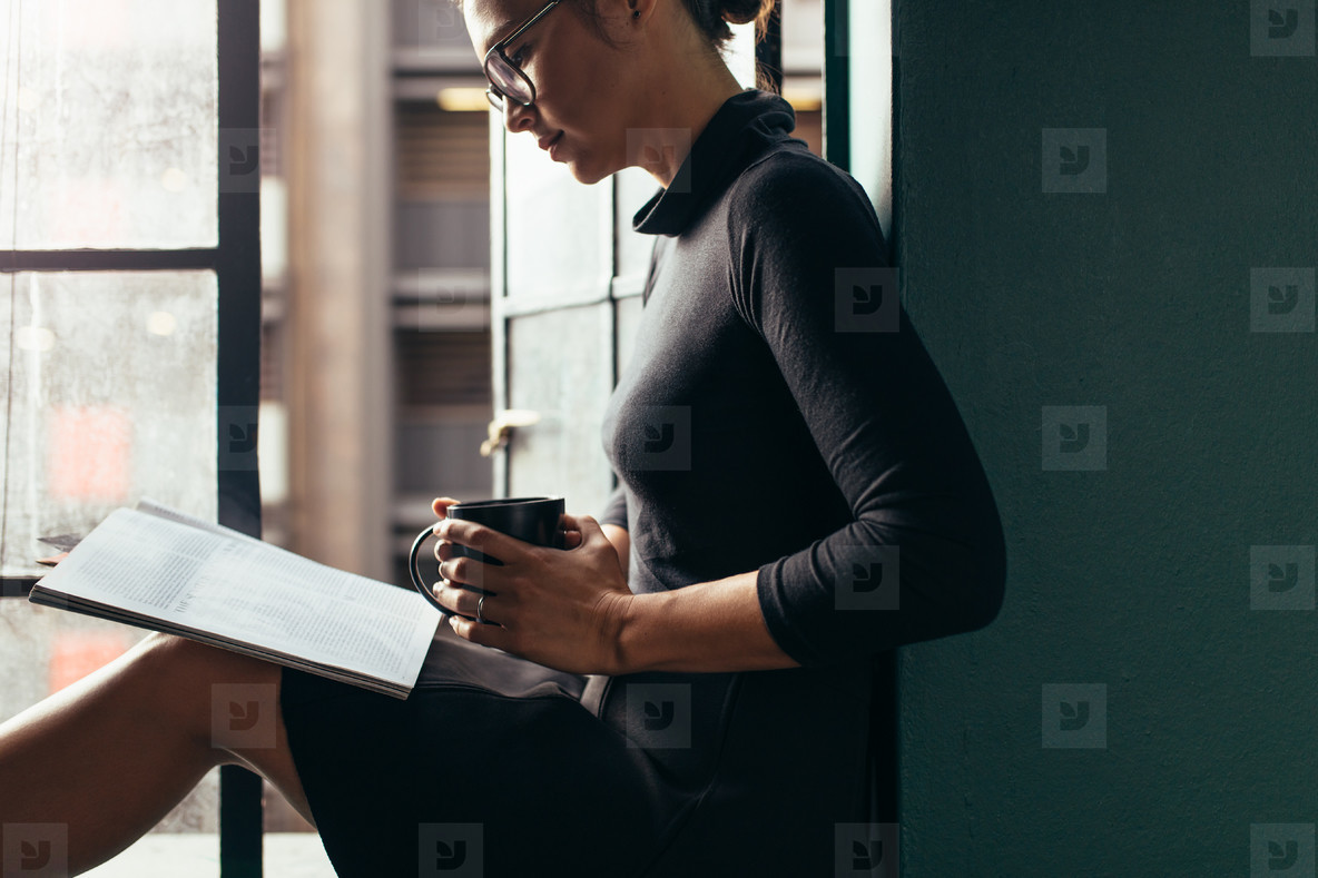Relaxed woman on window sill reading a book