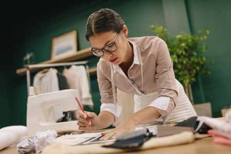 Female tailor designing clothes pattern on paper