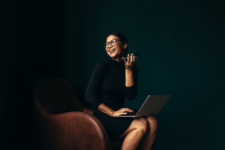 Businesswoman with laptop talking on mobile phone