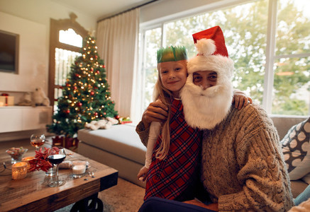Beautiful little girl with santa claus at home
