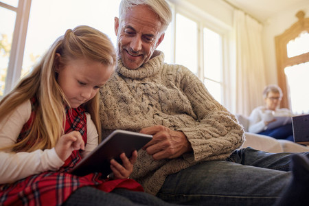 Senior man with granddaughter using digital tablet at home