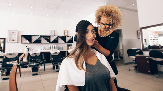 Female hair stylist working on a woman 039s hair at salon