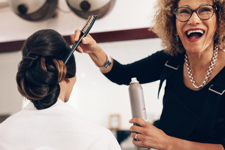 Happy looking hair stylist working at salon