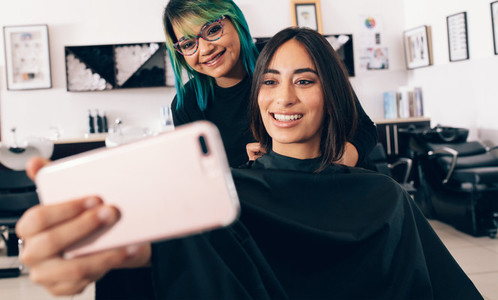 Women looking at mobile phone at salon