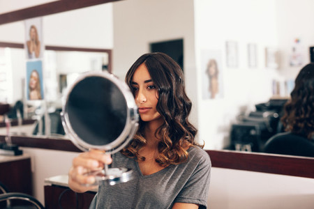 woman in salon with curled hairstyle looking herself in mirror