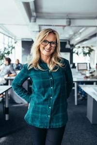 Smiling mature female standing in office