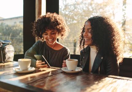Two women having fun at a coffee shop