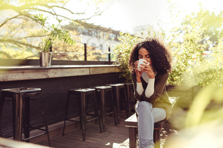 Woman drinking coffee at a coffee shop