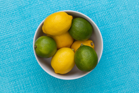Lemon and lime in bowl on blue background