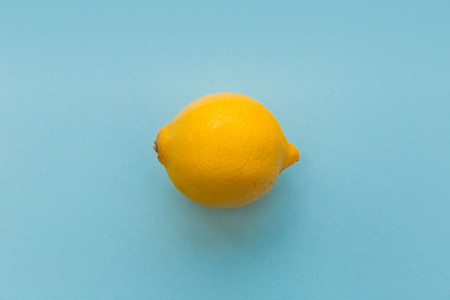 Yellow lemon fruit on bright blue background
