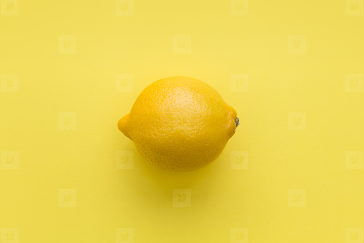 Lemon fruit on bright yellow background