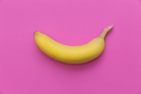 Yellow banana on bright pink background