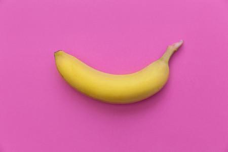 Yellow banana on bright pink background