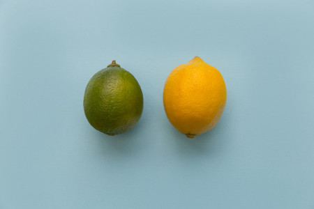 Lemon and lime fruits on bright blue background