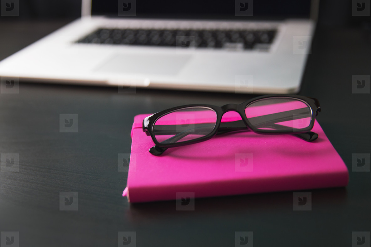 Notebook  reading glasses and laptop computer on black desk