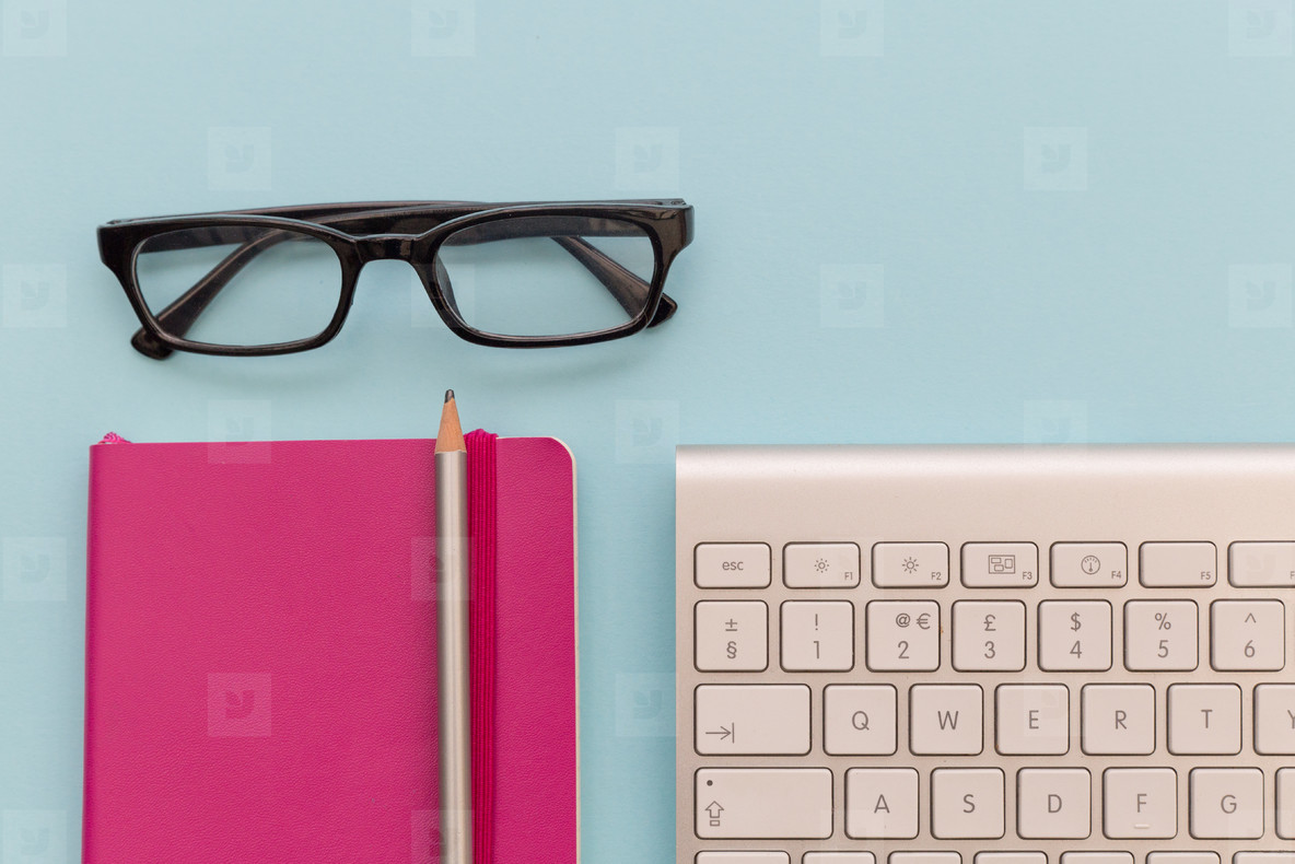 Computer keyboard  glasses and notebook on blue background works