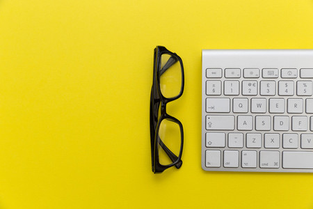 Computer keyboard   reading glasses on bright yellow background