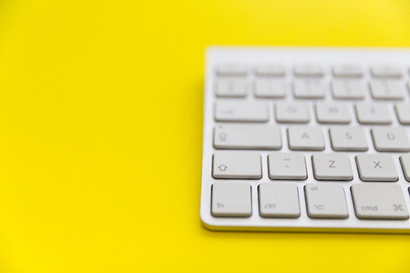 Wireless computer keyboard on bright yellow background