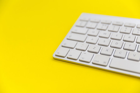 Computer keyboard on bright yellow background