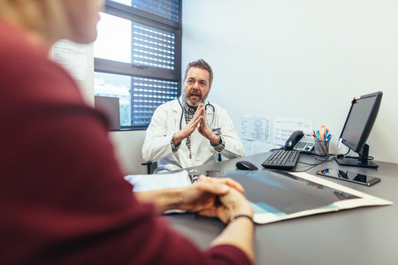 Doctor discussing with female patient in his clinic