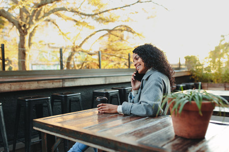 Woman sitting at a coffee shop talking over phone