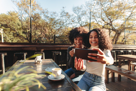 Two women having fun taking a selfie outdoors