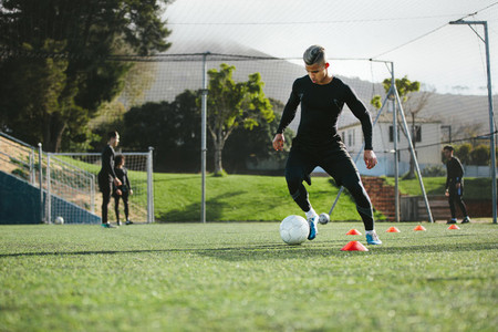 Football player practice dribbling on field