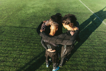 Soccer team standing in a huddle