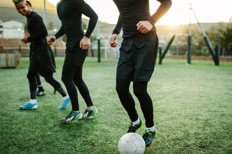 Teenagers practicing football on field