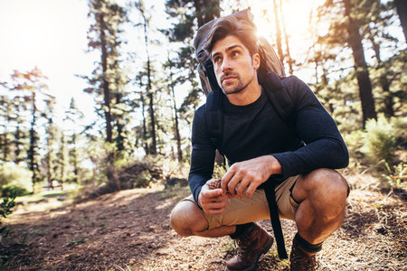 Man sitting on forest trail wearing a backpack