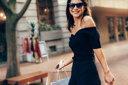 Trendy woman on city road with shopping bags