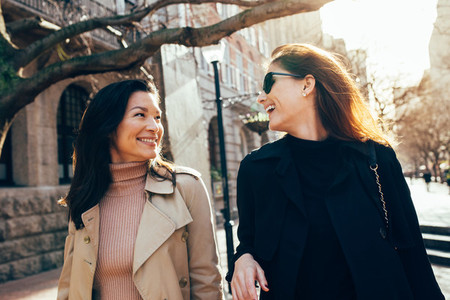 Female friends on walking down the street and smiling