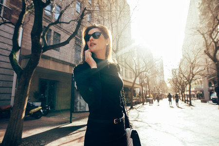 Stylish female walking on city street and talking on phone