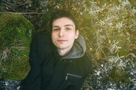 Young man lying down in nature