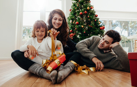 Small family having fun opening Christmas gifts