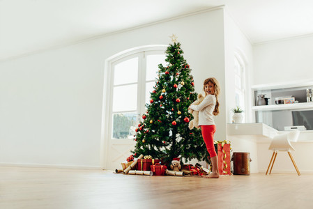 Little girl standing near Christmas tree at home