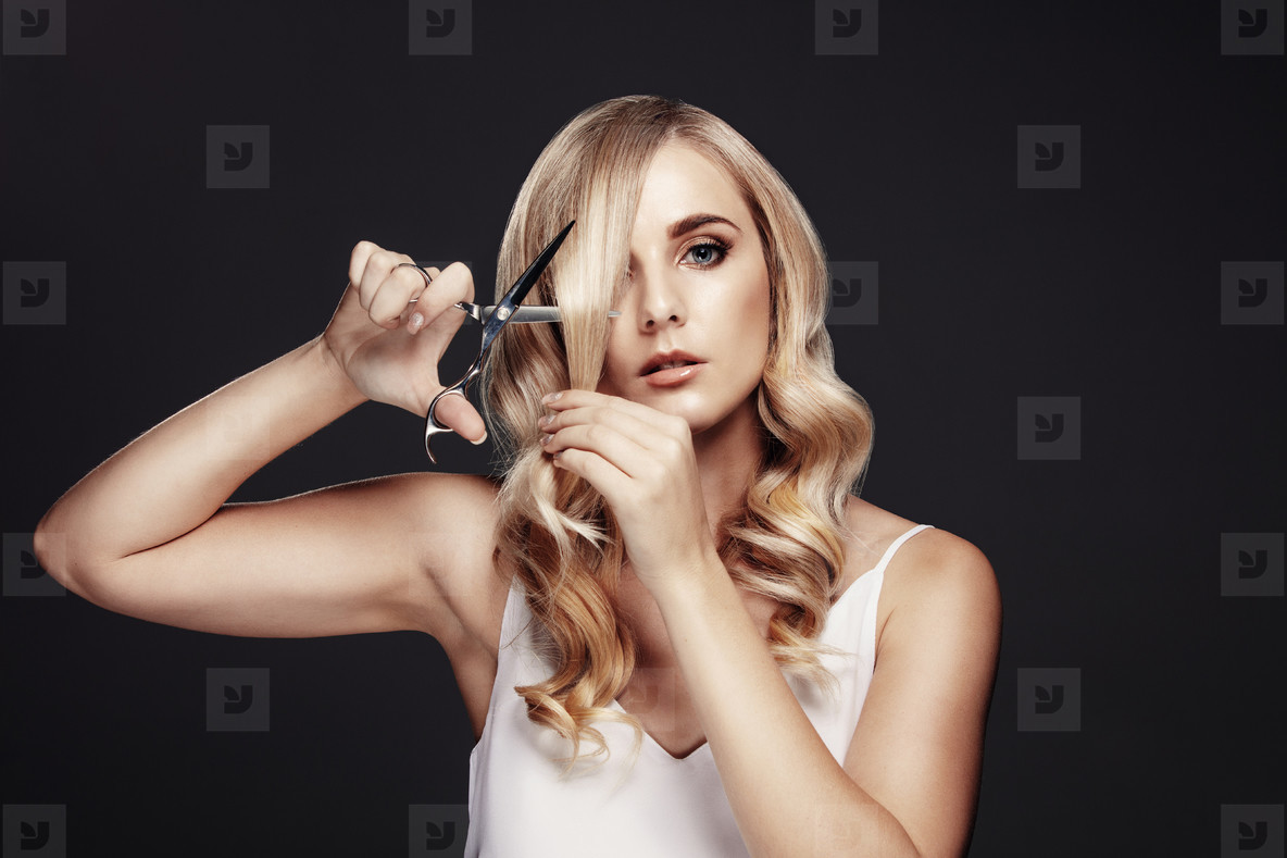 Photos attractive young woman cutting her own hair youworkforthem