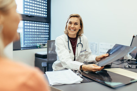Smiling doctor holding x ray communicating with patient
