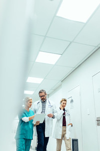 Group of physicians walking in hospital corridor and discussing