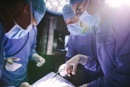 Female surgeon with her team performing surgery on patient
