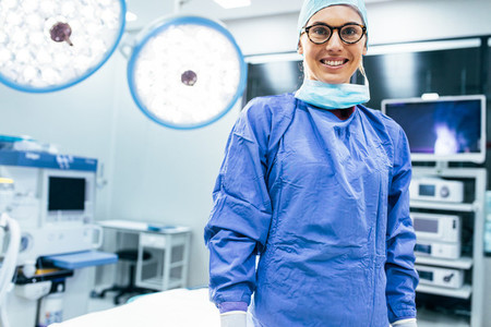 Smiling female surgeon in surgical uniform at operating room