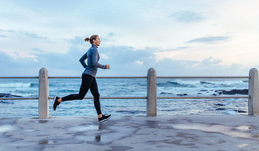 Fitness woman running on a road by the sea