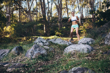 Athlete jogging through rough terrain in forest