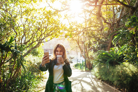 Woman clicking a selfie in park holding a coffee glass
