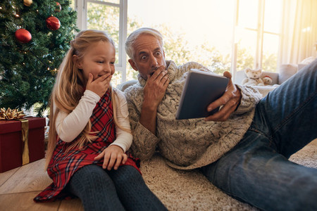 Surprised grandfather and granddaughter looking at digital table